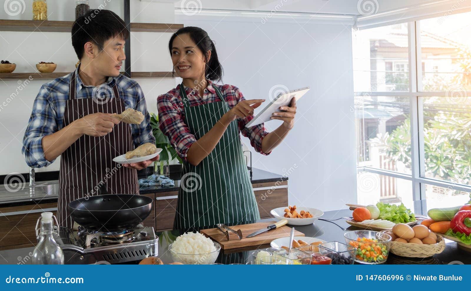 Le giovani coppie asiatiche sono felici di cucinare insieme, due famiglie stanno aiutando a preparare cucinare nella cucina