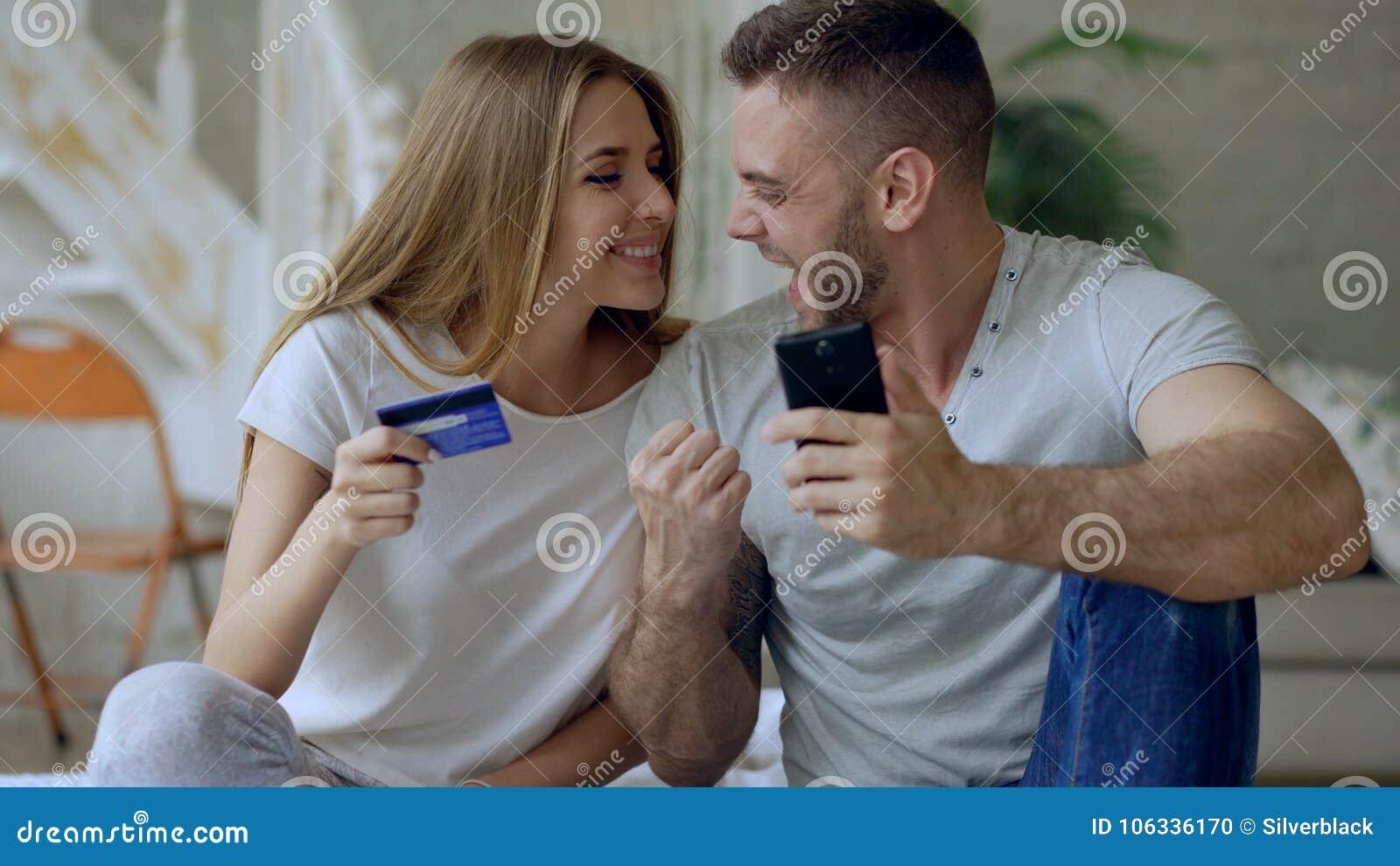Le giovani coppie attraenti con lo smartphone e l acquisto della carta di credito su Internet si siedono sul letto a casa