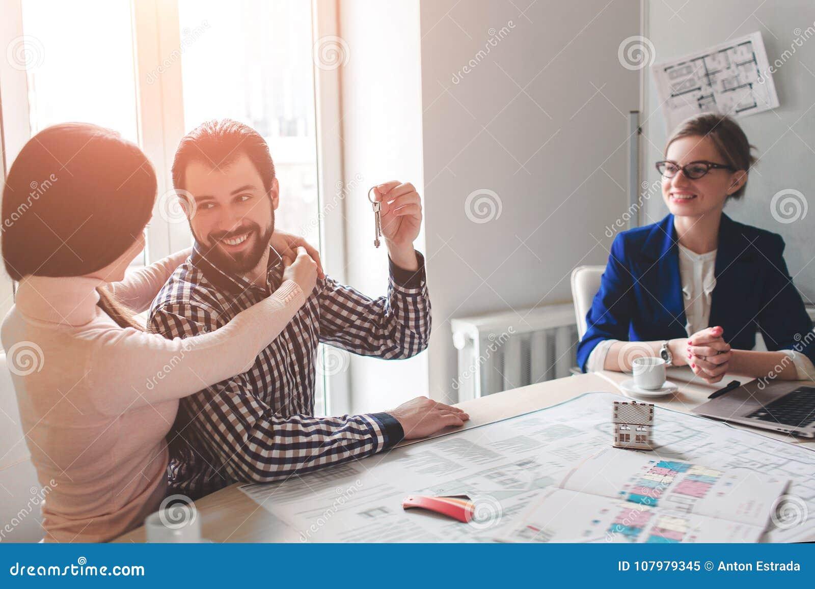 Le giovani coppie della famiglia acquistano il bene immobile della proprietà di affitto Agente che dà consultazione all uomo ed a