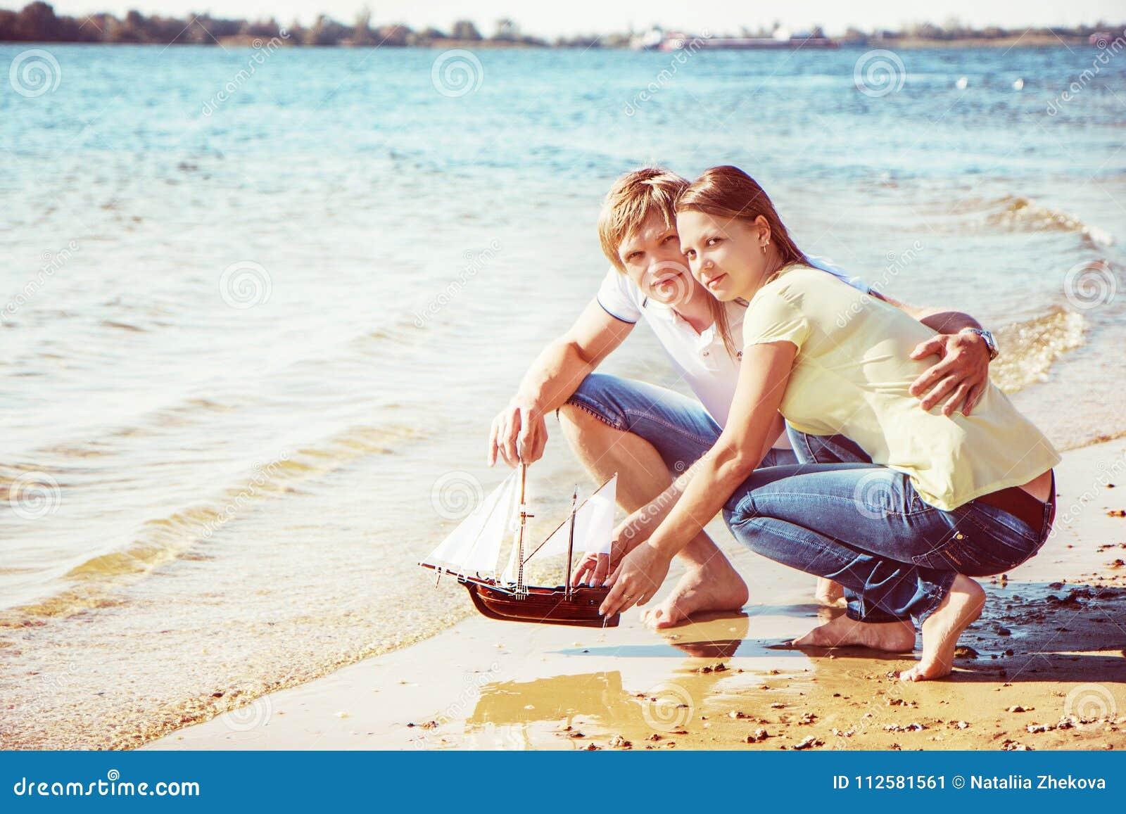 Le giovani coppie felici che godono del picnic sulla spiaggia ed hanno buon Ti