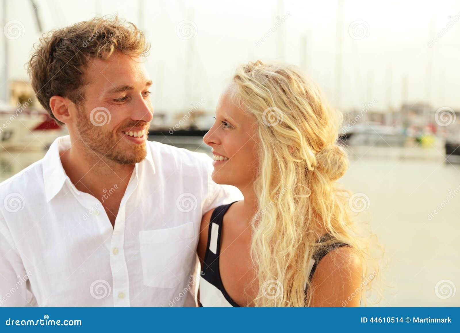 Le giovani coppie felici in yacht harbor il porto del porticciolo