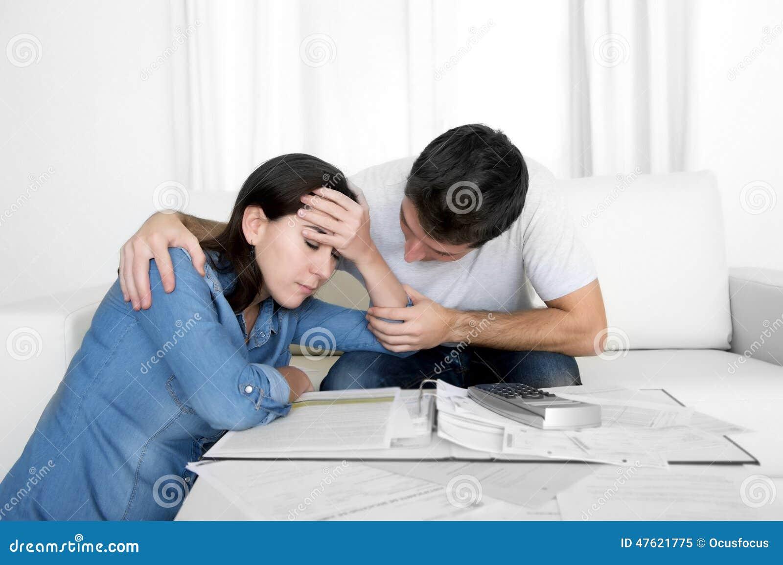 Le giovani coppie si sono preoccupate a casa nel marito di sforzo che conforta la moglie nei problemi finanziari