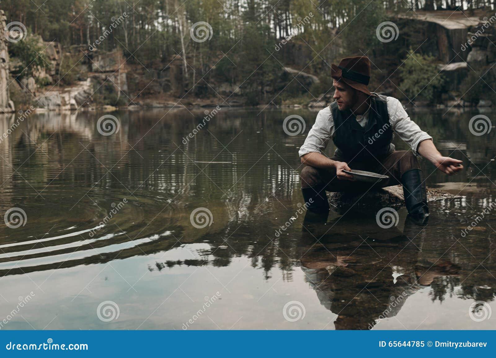 Le golddigger Unshaved lave l or dans le lac avec la banque rocheuse