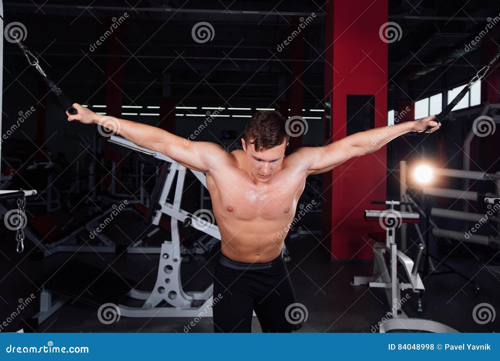 Le grand bodybuider fort sans chemises démontrent des exercices de croisement Les muscles pectoraux et la formation dure