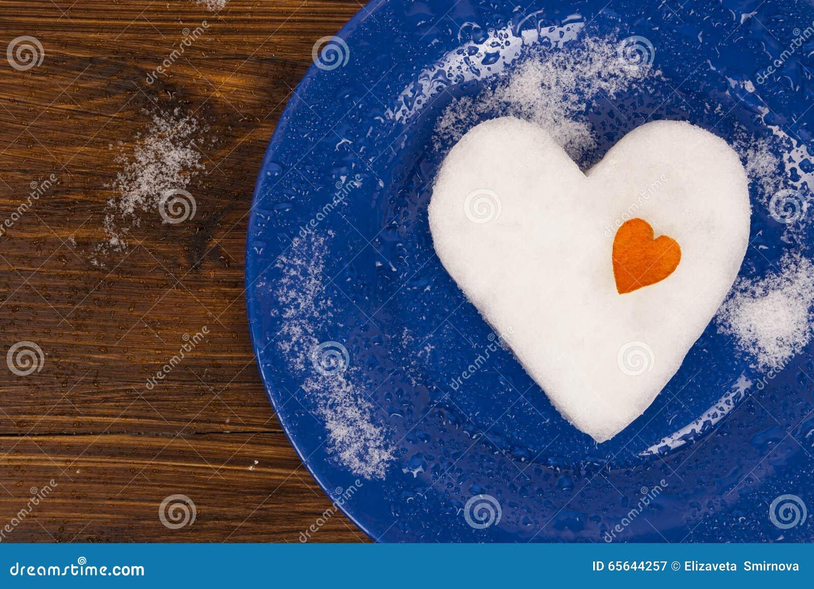 Le grand coeur de neige décoré du petit coeur orange se trouvant du plat bleu
