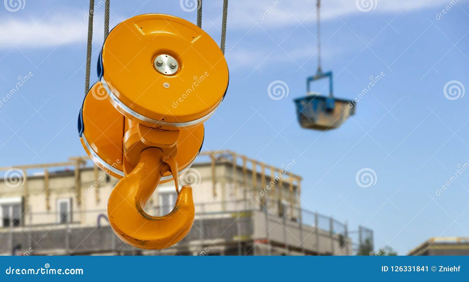 Le grand crochet devant un récipient bleu avec des matériaux de construction flotte au-dessus du chantier de construction avec la