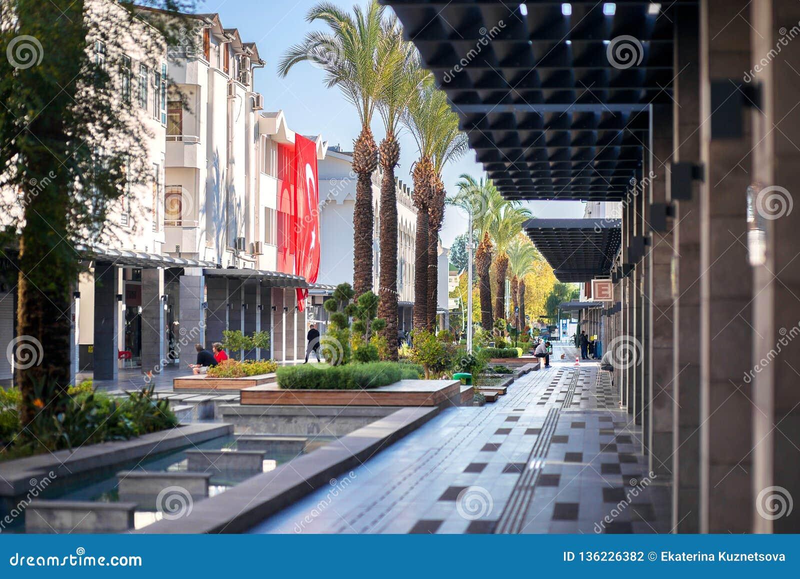 Le grand drapeau turc rouge accroche sur une de maisons La rue turque piétonnière avec la fontaine dans la ville de Kemer
