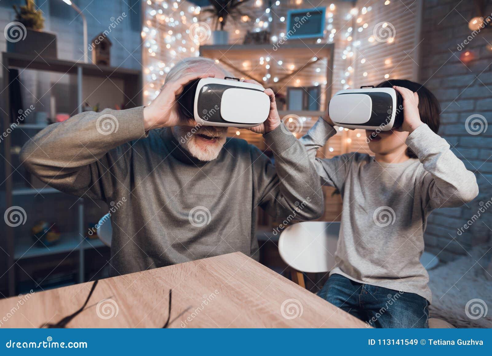 Le grand-père et le petit-fils emploient la réalité virtuelle la nuit à la maison