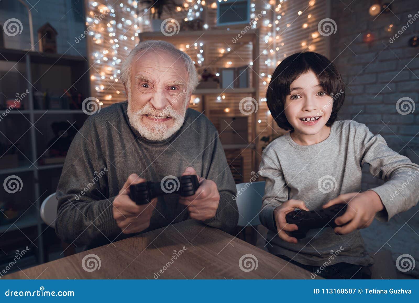 Le grand-père et le petit-fils jouent des jeux vidéo la nuit à la maison