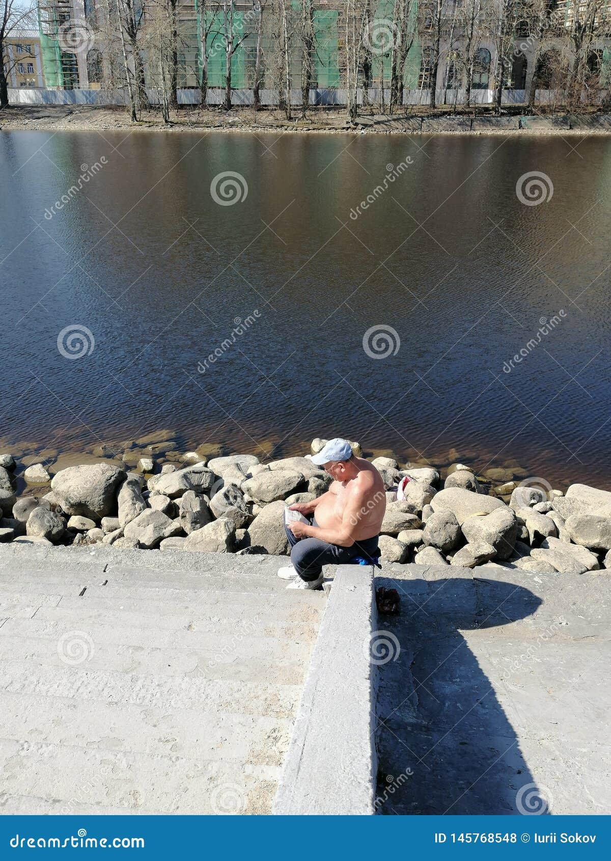 Le grand-père lit un journal sur le canal