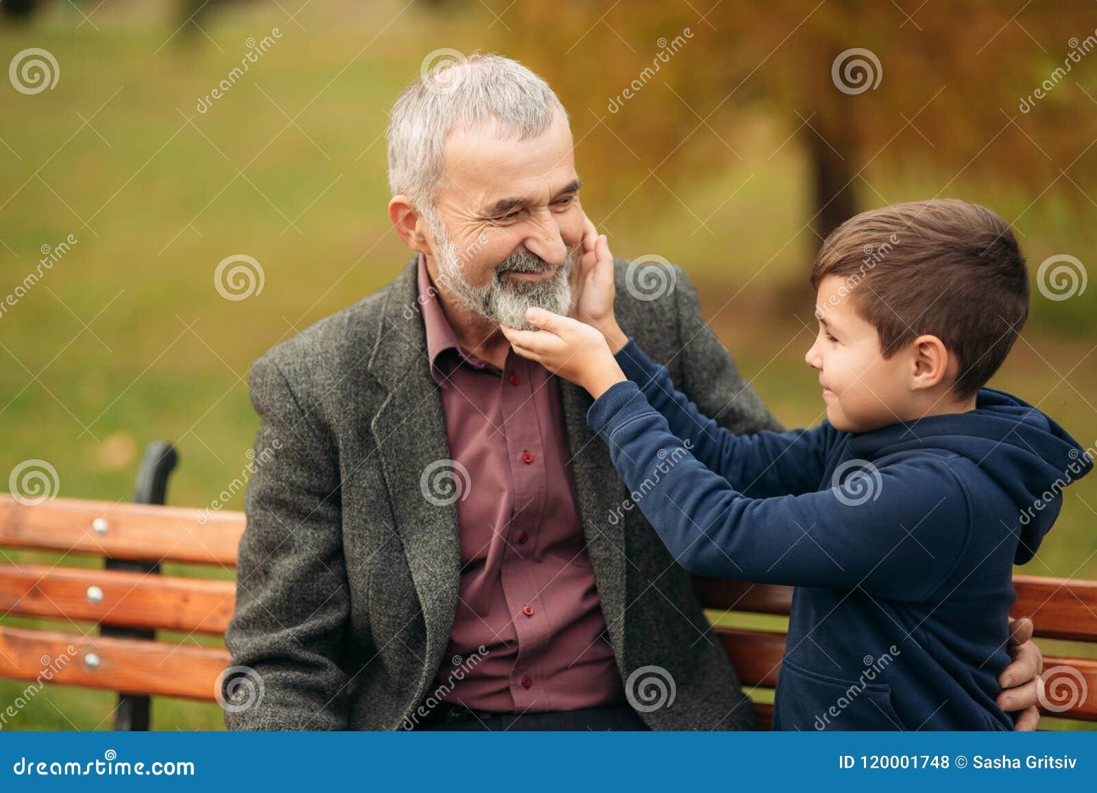 Le grand-papa et son petit-fils passent le temps ensemble en parc Ils se reposent sur le banc Marche en parc et