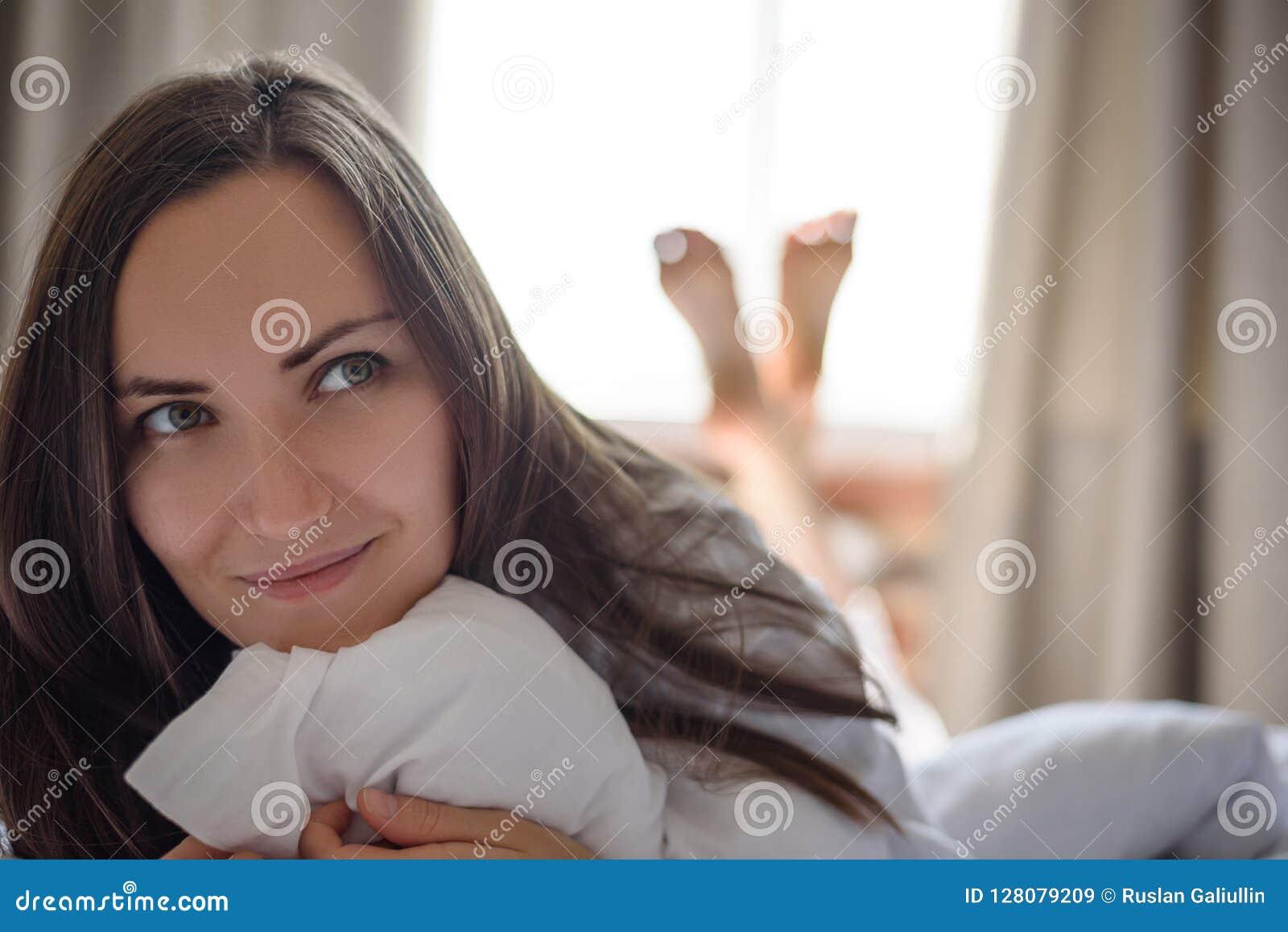 Le grand portrait frontal d une jeune femme dans le début de la matinée de lit, se réveillent, bonjour, l espace de copie