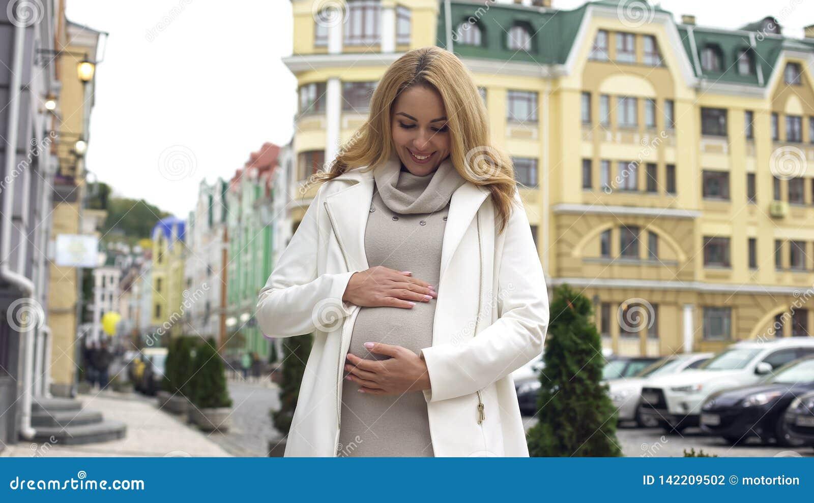 Le gravida kvinnan som ser hennes buk som slår ömt det, moderskap