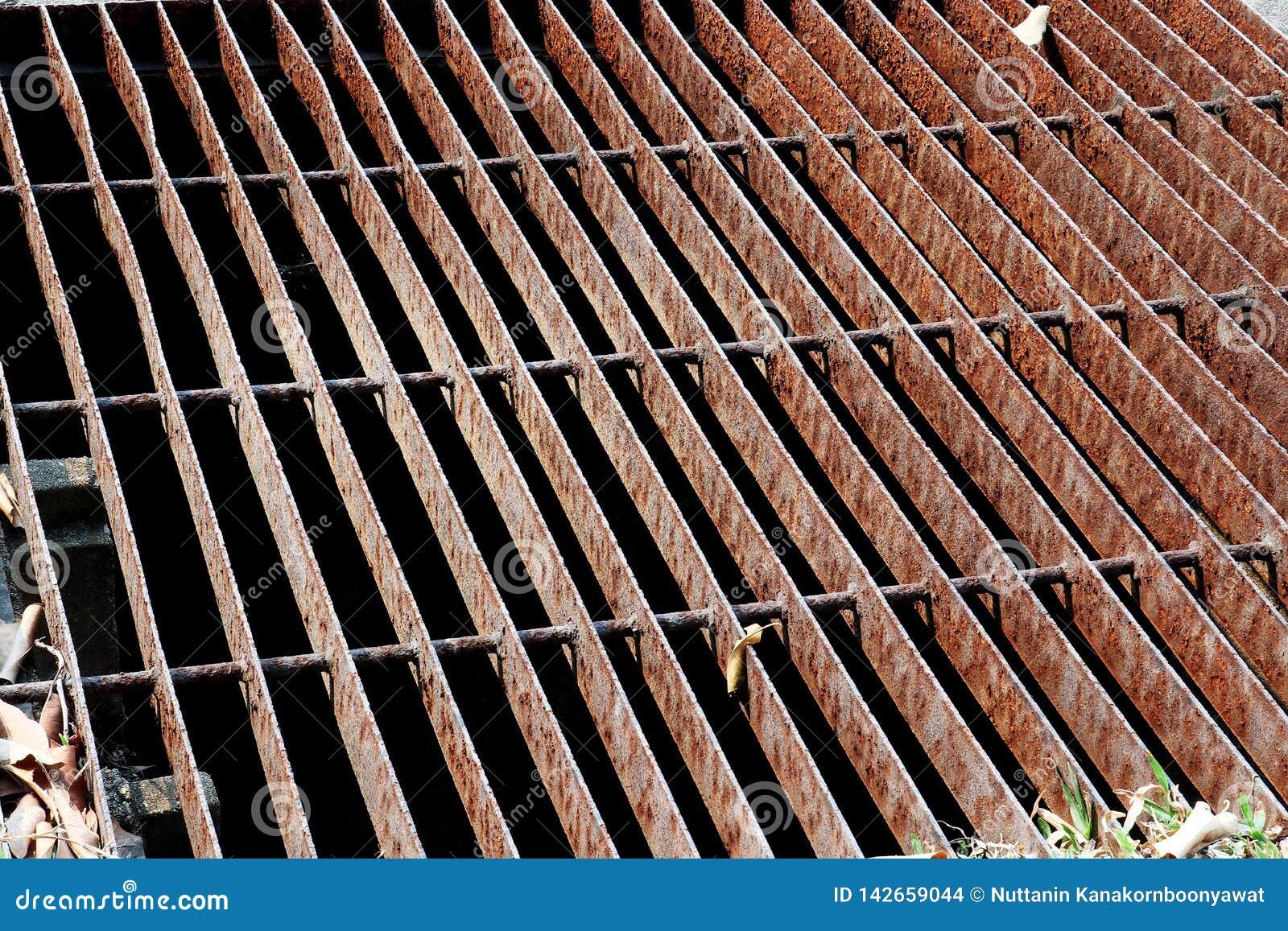 Le grondaie vuotano la griglia, copertura dello scolo Scoli della strada - copertura della fogna Griglia del ferro dello scolo de