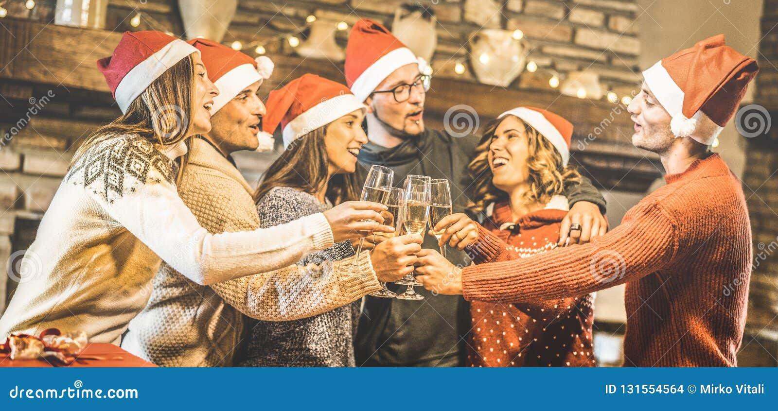 Le groupe d amis avec des chapeaux de Santa célébrant Noël avec du vin de champagne grillent à la maison le dîner - concept de va