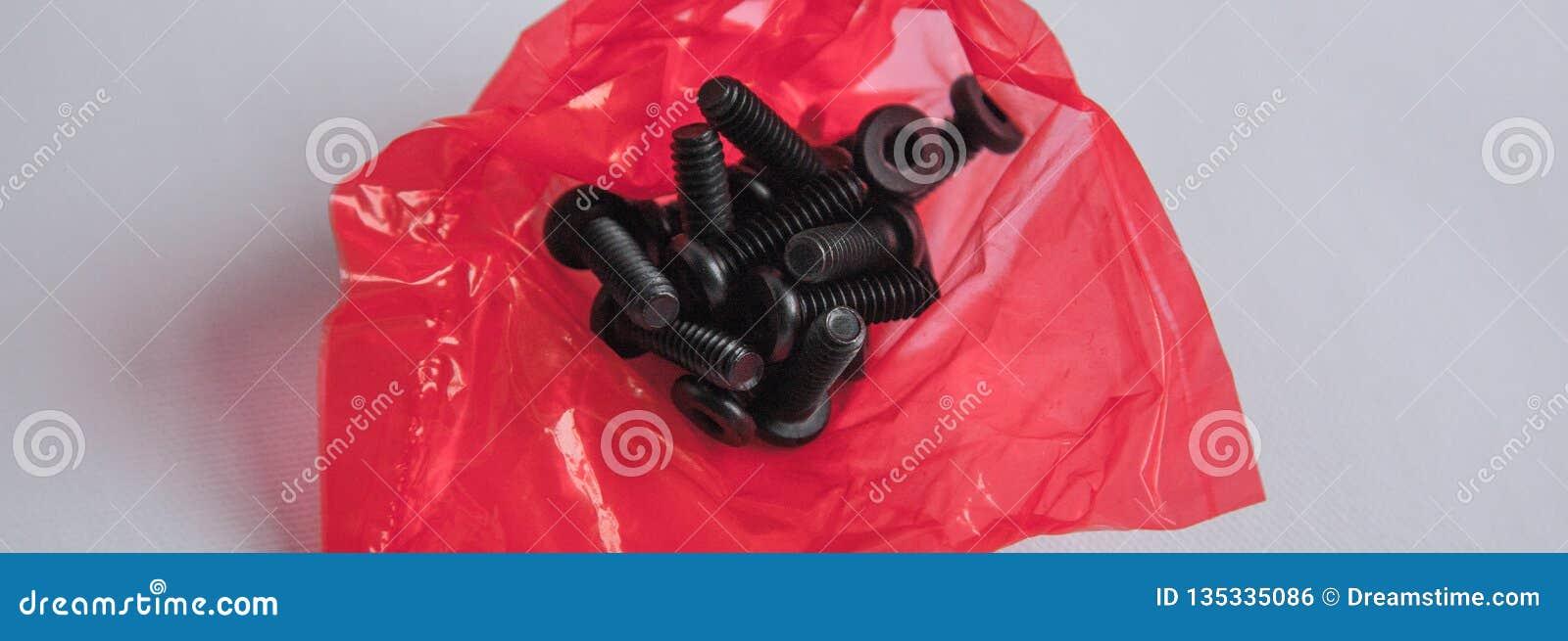 Le groupe de boulons dans le sachet en plastique rouge