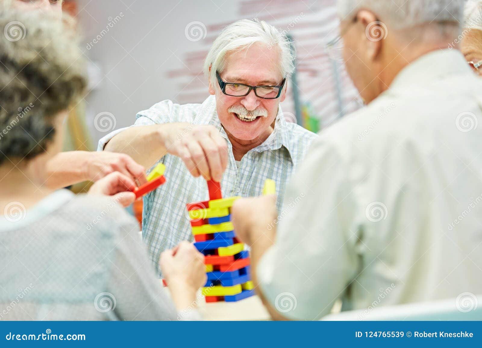 Le groupe de démence dans la maison de retraite joue avec les blocs constitutifs