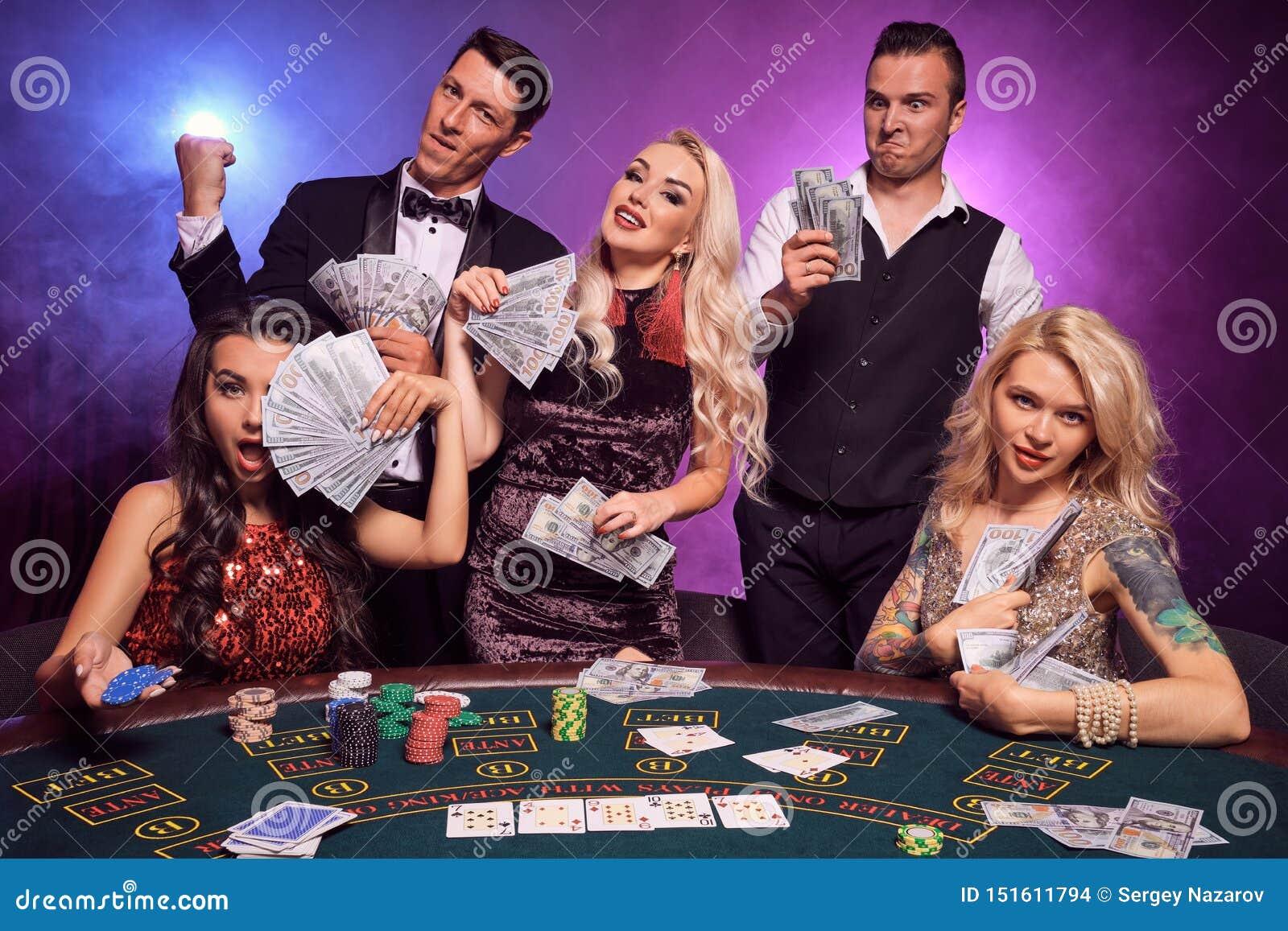 Le groupe de de jeunes amis riches jouent au poker à un casino