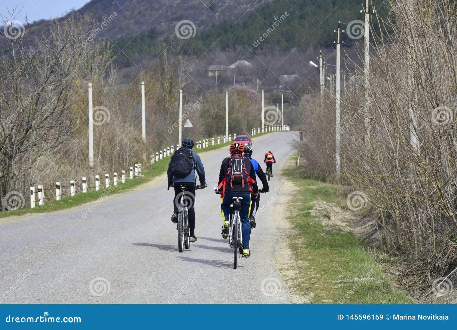 Le groupe de jeunes cyclistes conduisent le long d une route goudronnée