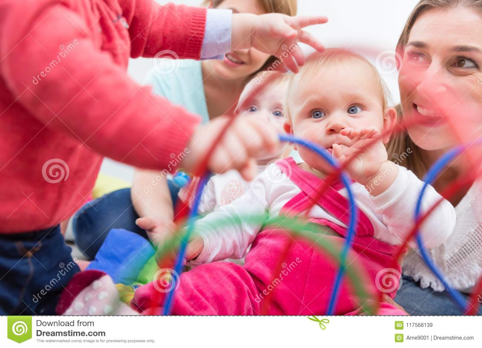 Le groupe de jeunes mères heureuses observant leurs bébés mignons et en bonne santé jouent