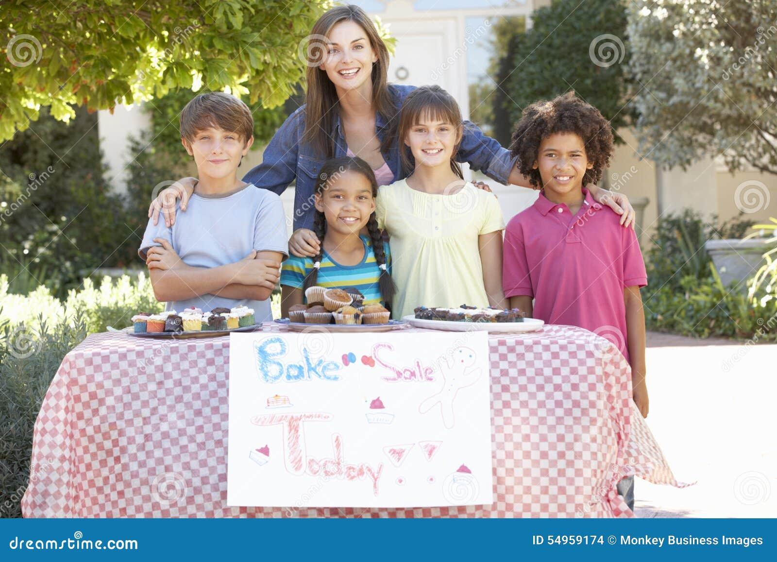 Le groupe de se tenir d enfants font la vente cuire au four avec la mère