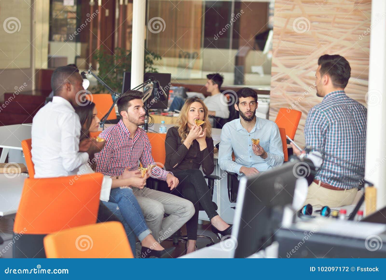 Le groupe des jeunes dans le bureau moderne ont la réunion et la
