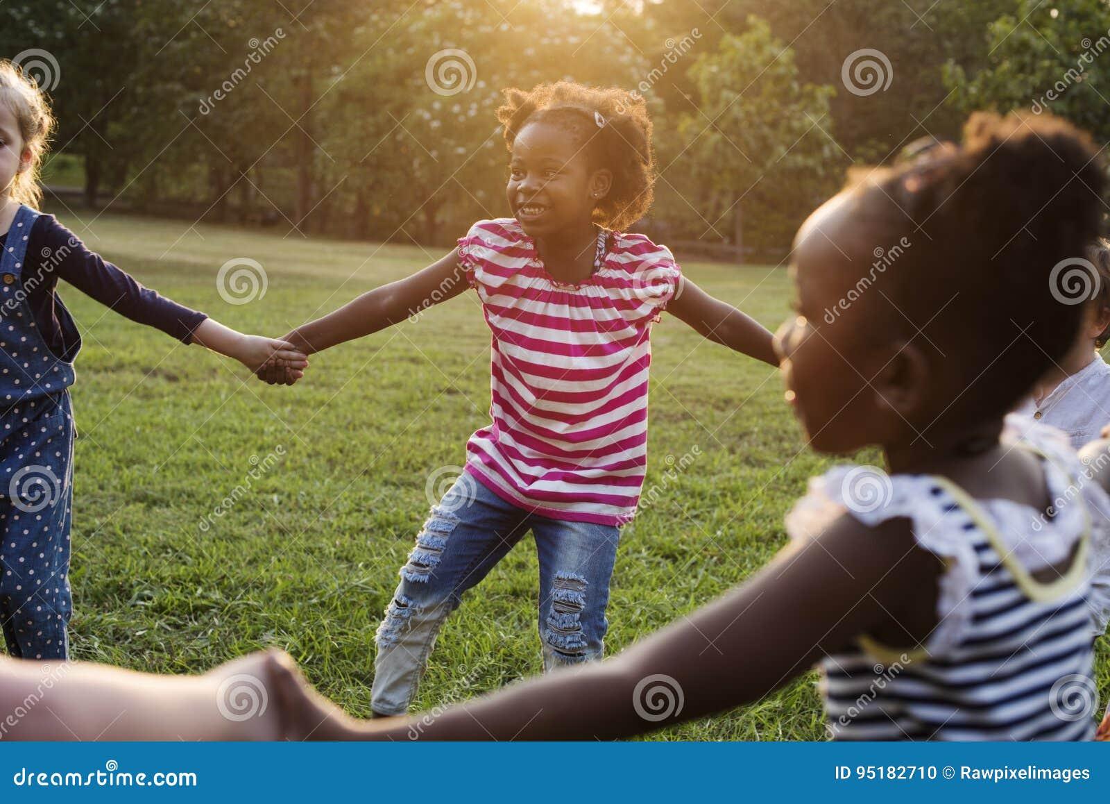 Le groupe du jardin d enfants badine des amis tenant des mains jouant au parc