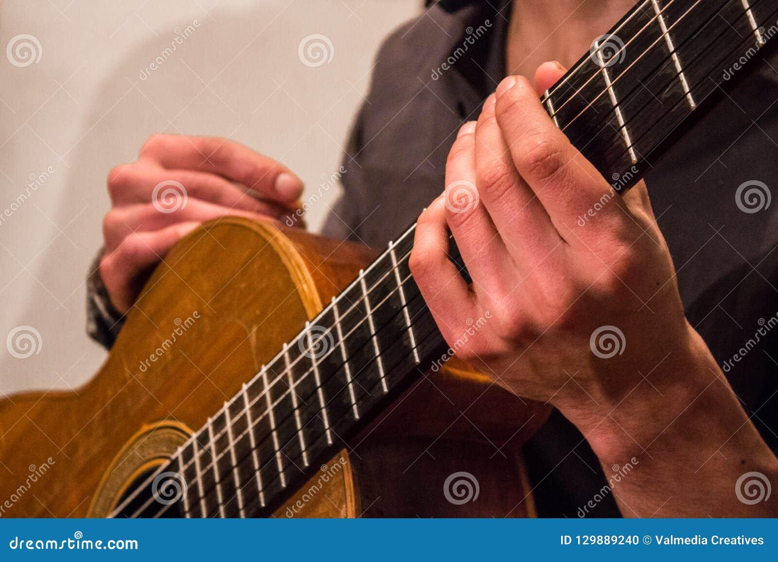 Le guitariste de l appartenance ethnique mélangée tient une vieille guitare classique faite main