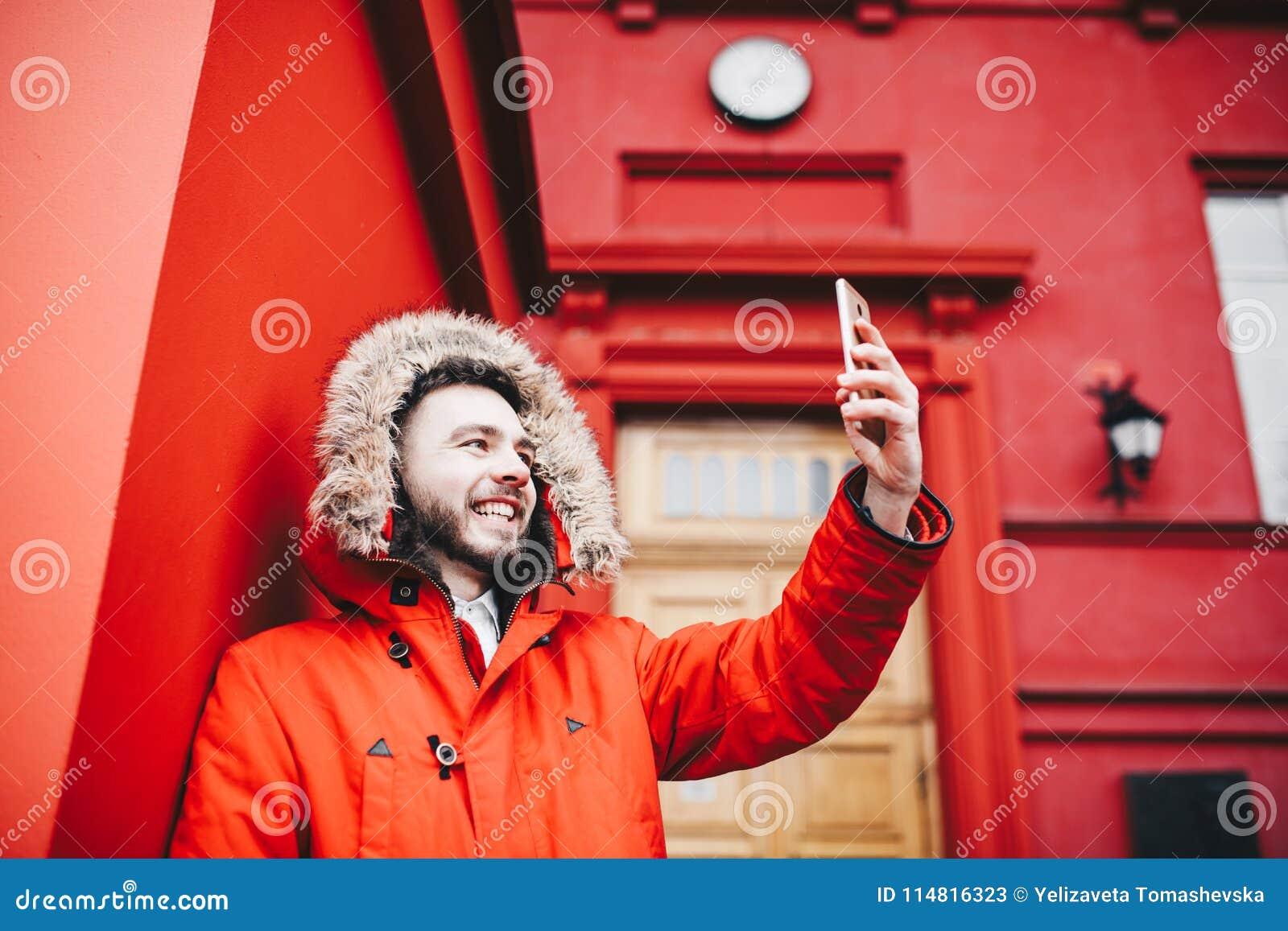 Le jeune étudiant masculin beau avec le sourire et la barbe se tient sur le mur rouge de fond, façade d établissement d enseignem