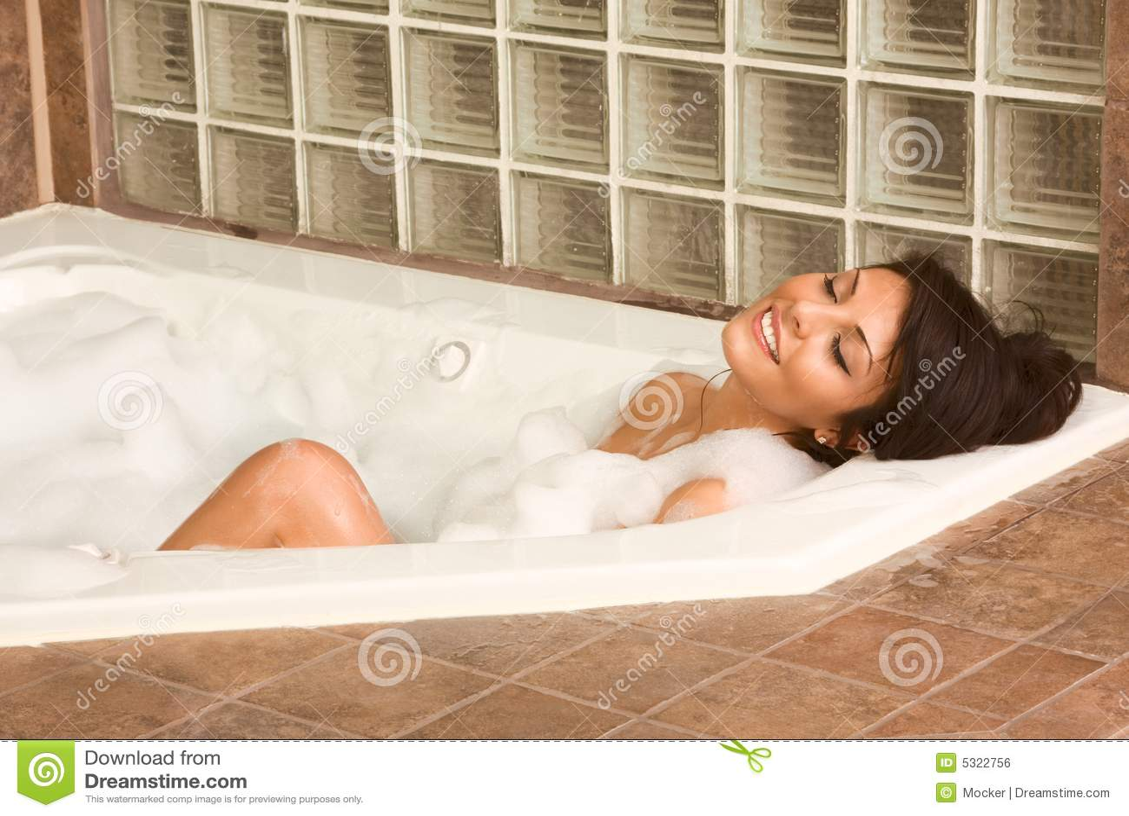 Le jeune attrayant gorge la femme prenant le bain de mousse