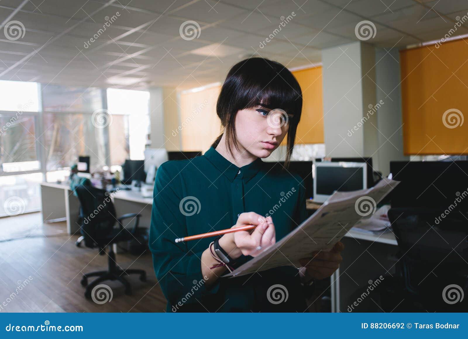 Le jeune bel employé de bureau de fille regardant des papiers d
