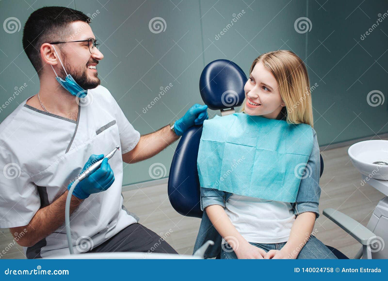 Le jeune client féminin heureux s asseyent dans la chaise en art dentaire Elle regardent le dentiste et le sourire Jeune homme da