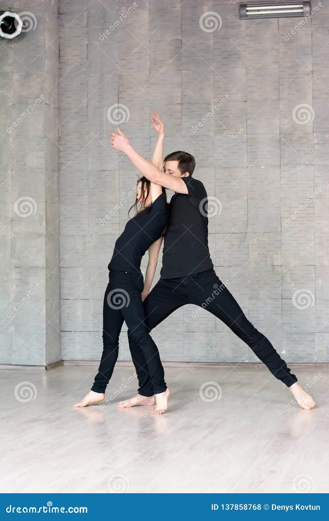 Le jeune couple dans le noir danse