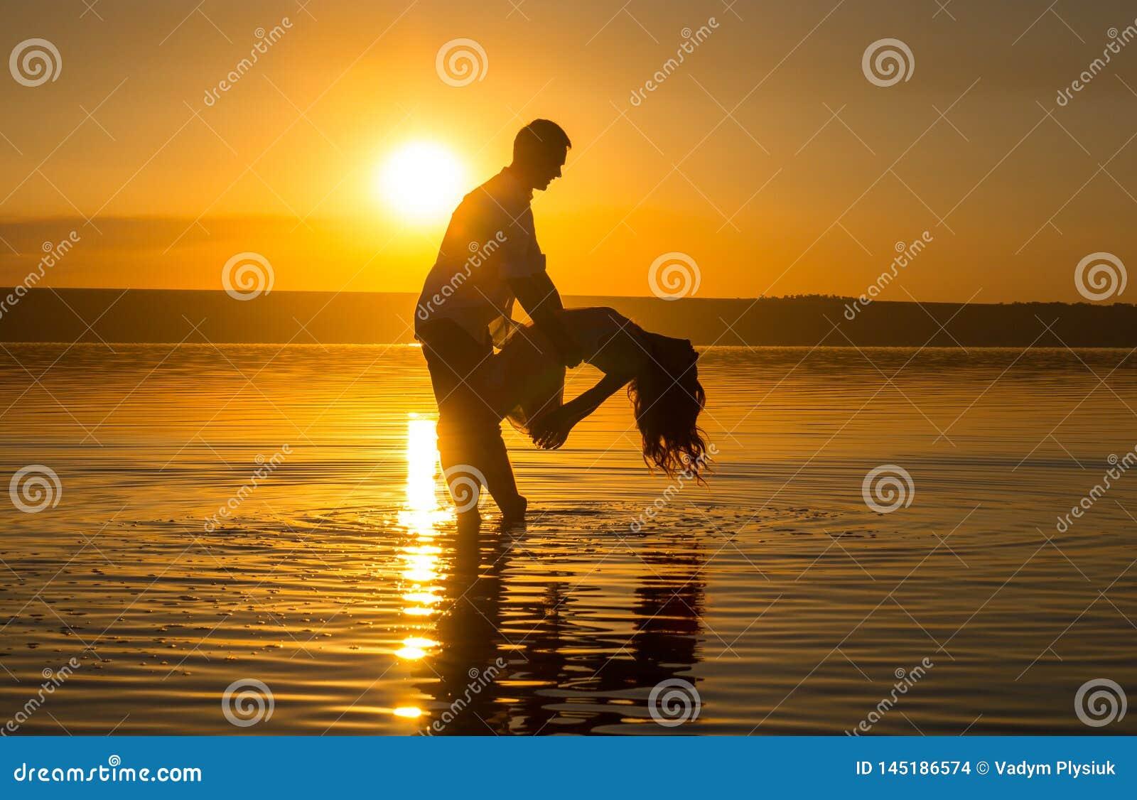 Le jeune couple danse dans l eau sur la plage d ?t? Coucher du soleil au-dessus de la mer Deux silhouettes contre le soleil Calme