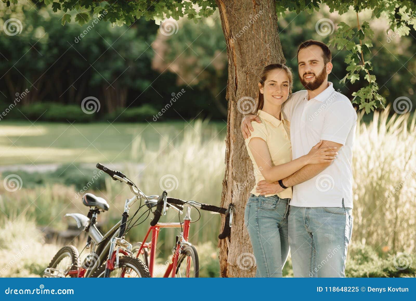 Le jeune couple des cyclistes étreint dehors