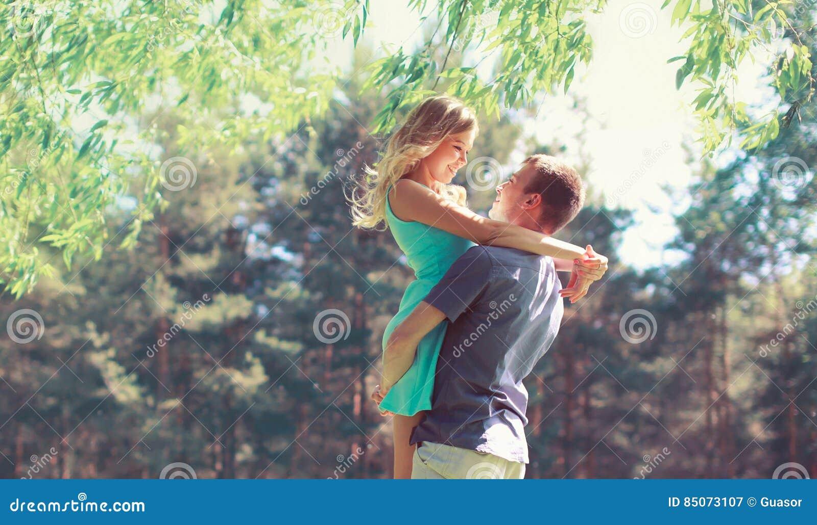 Le jeune couple heureux dans étreindre d amour apprécie la journée de printemps, homme affectueux se tenant dessus remet à sa fem