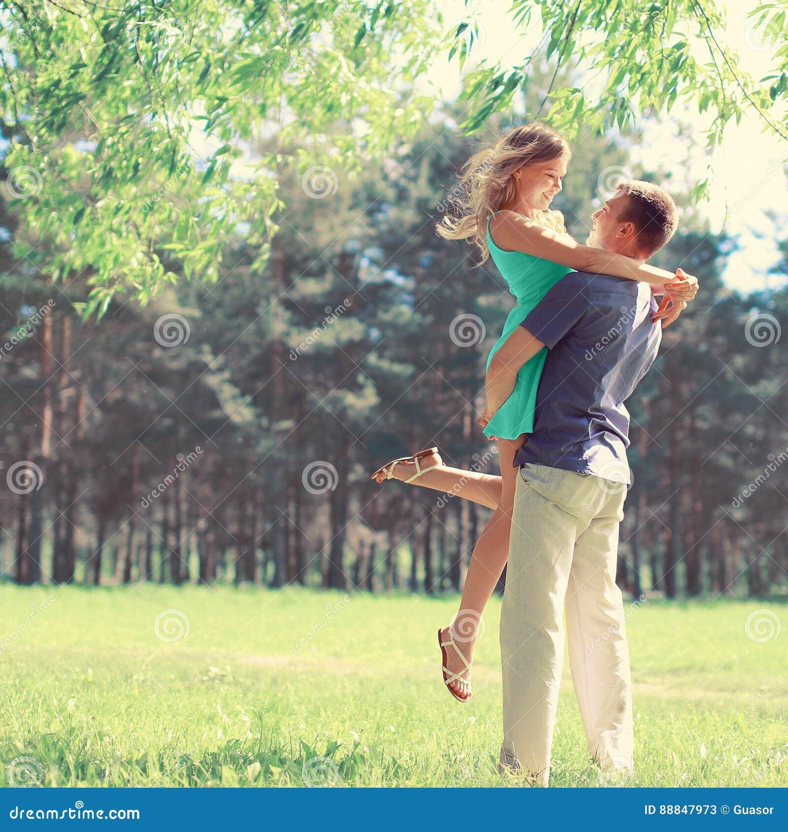 Le jeune couple heureux dans l amour apprécie la journée de printemps, homme affectueux se tenant dessus remet à sa femme la marc