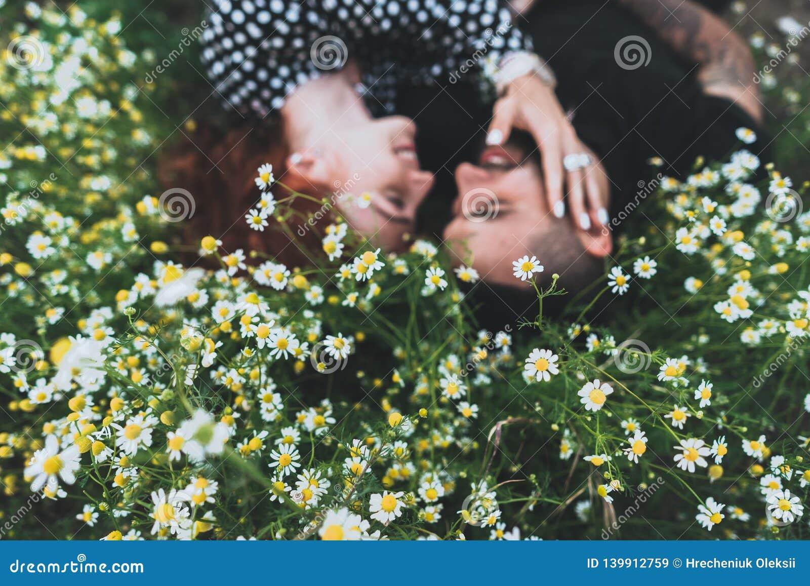 Le jeune couple se trouve sur le champ avec des marguerites