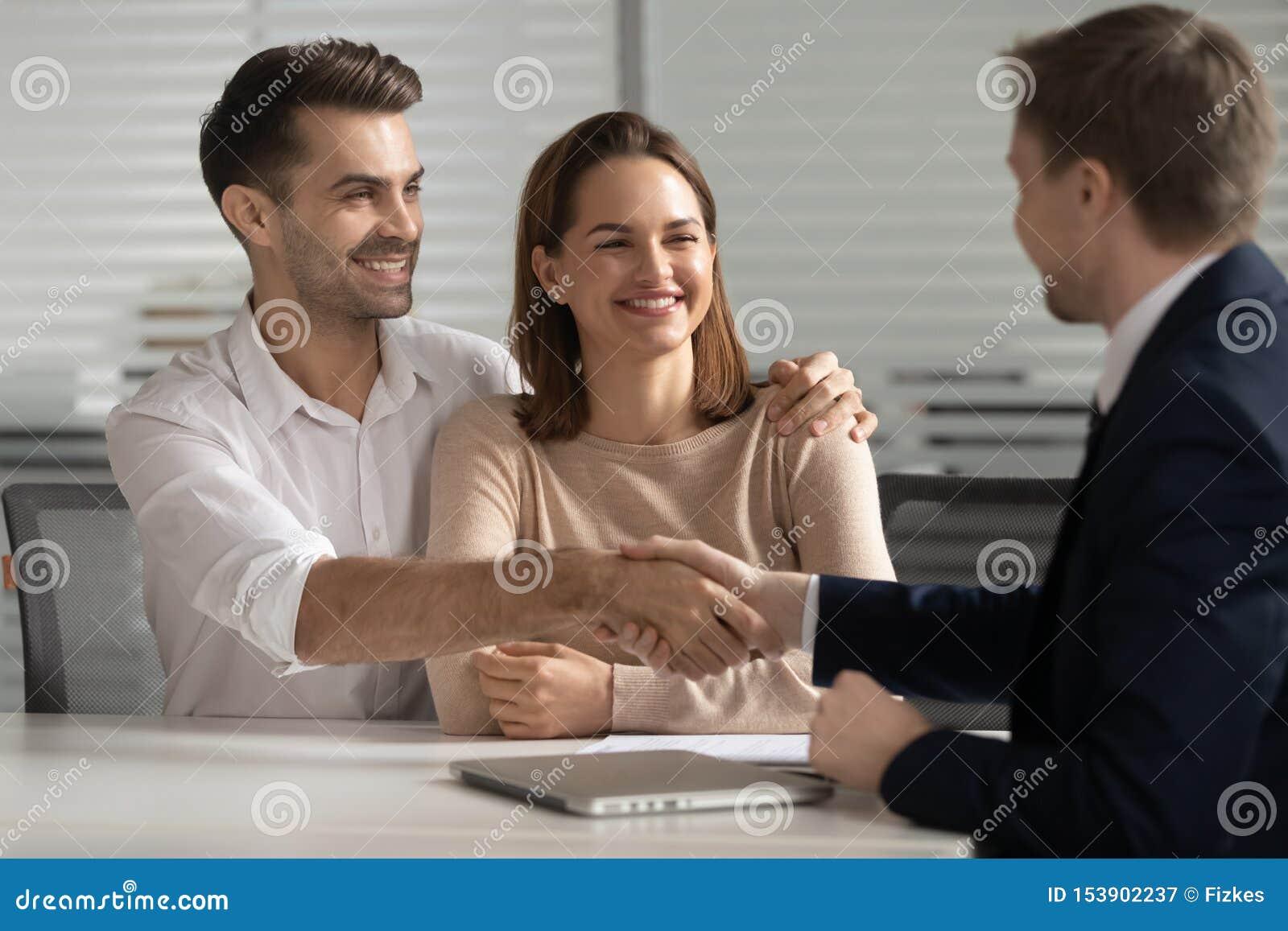 Le jeune courtier heureux d assureur d avocat de poignée de main de couples font l affaire d affaires