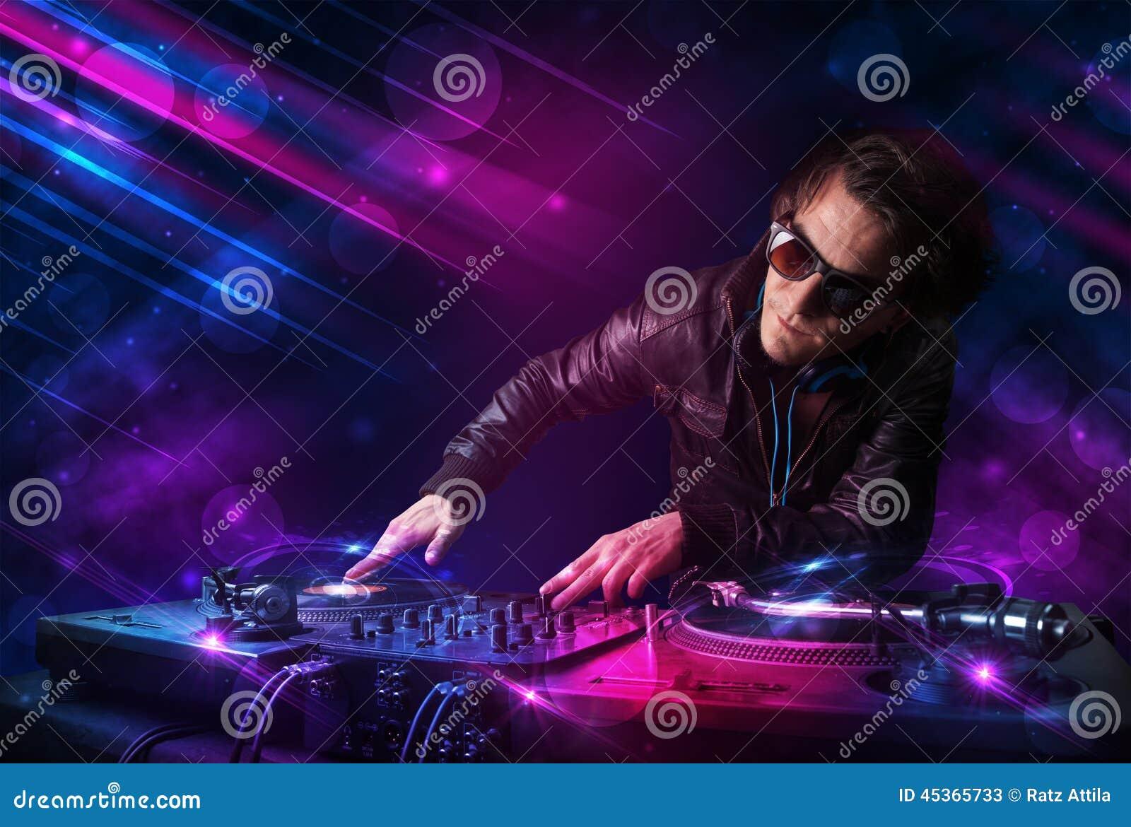 Le jeune DJ jouant sur des plaques tournantes avec des effets de la lumière de couleur