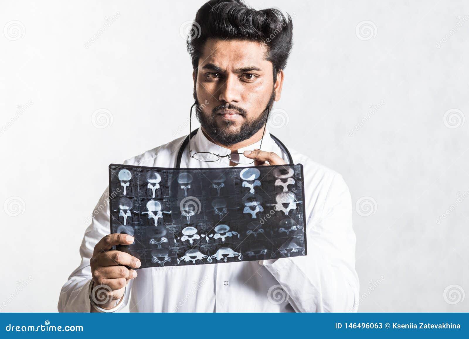 Le jeune docteur beau dans un manteau blanc avec un st?thoscope v?rifie attentivement le rayon X du patient