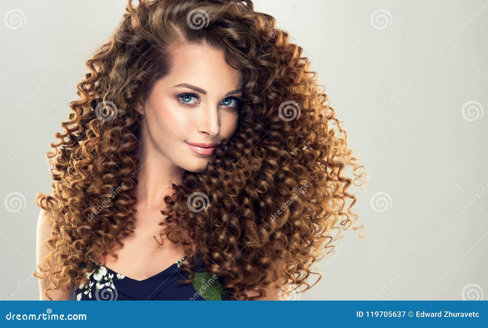 Le jeune, femme d une chevelure de brun avec dense, élastique se courbe dans une coiffure