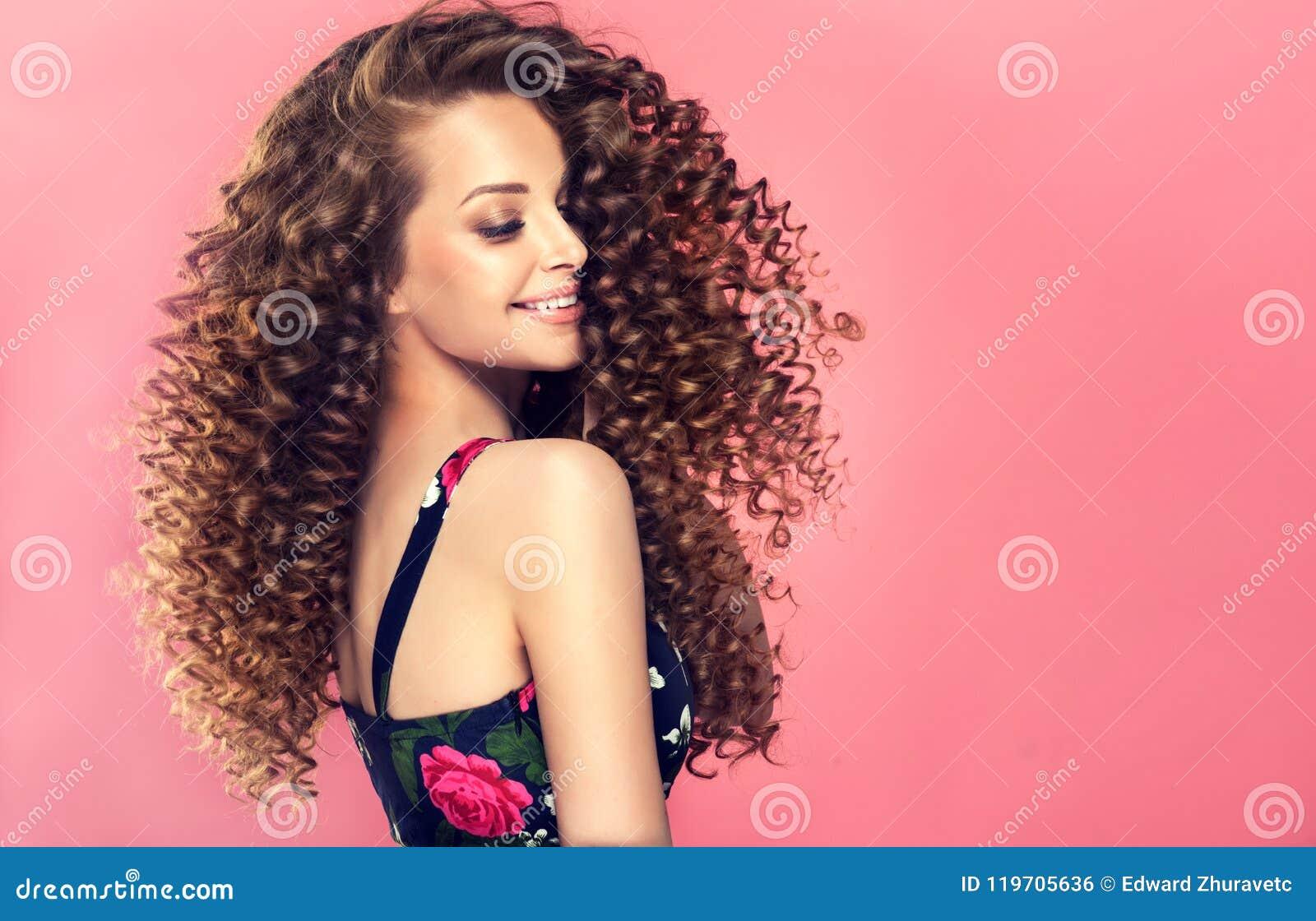 Le jeune, femme d une chevelure de brun avec dense, élastique se courbe dans une coiffure Verticale dans le profil