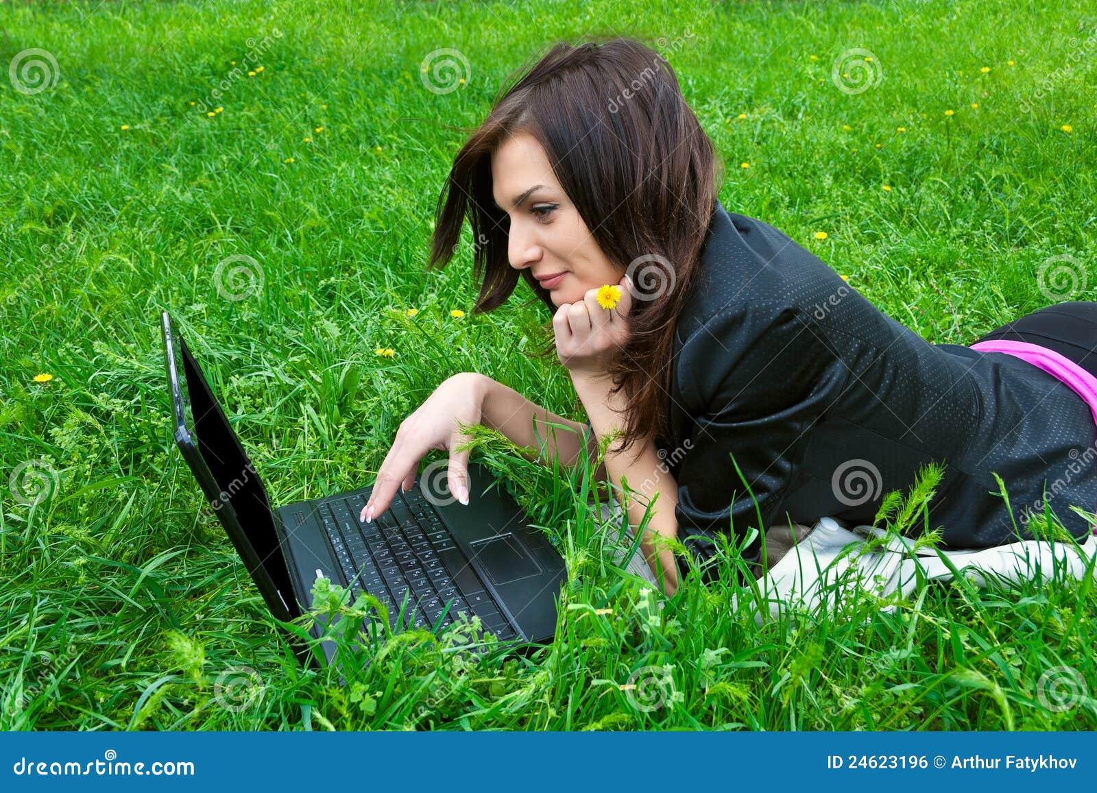 Le jeune femme travaille sur l ordinateur portatif.