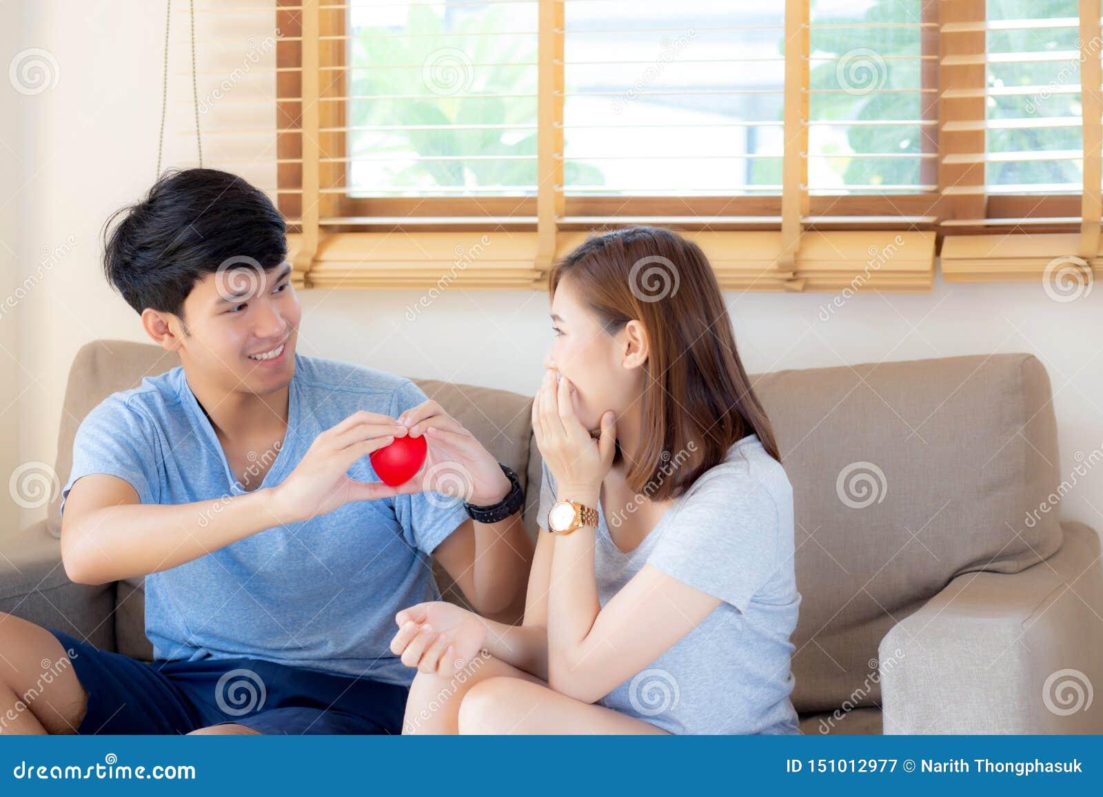 Le jeune geste asiatique de couples de beau portrait tenant la forme de coeur ensemble, mari donnent à épouse de forme de coeur l
