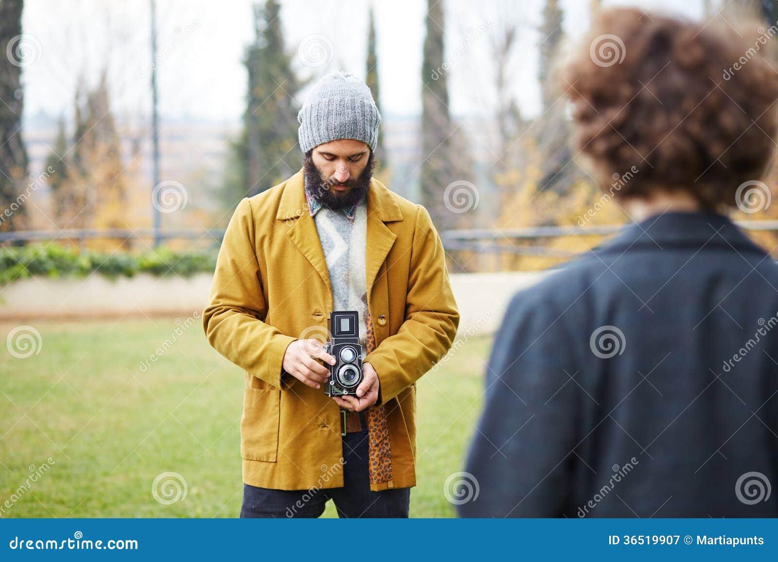 Le jeune hippie barbu prenant la photo à la fille rousse avec TLR est venu