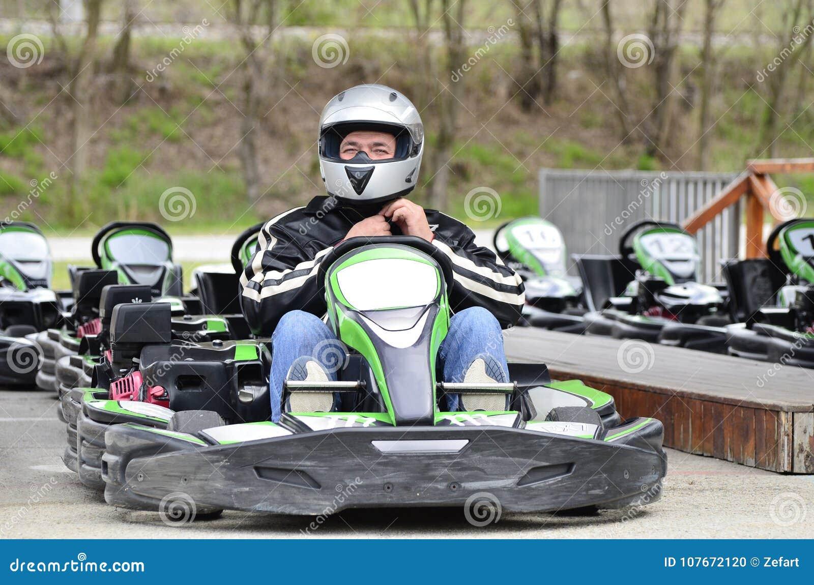 Le jeune homme ajustent le casque sur la voiture de kart sur une voie d emballage de terrain de jeu