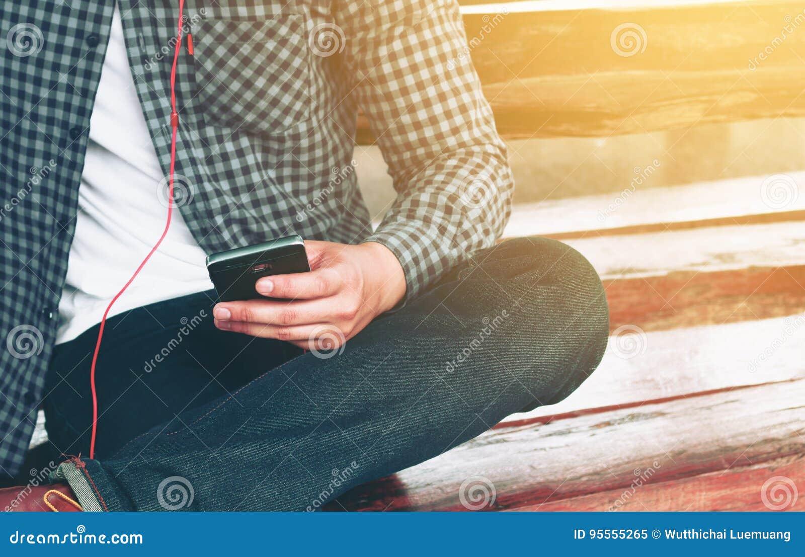 Le jeune homme asiatique dactylographiant sur le smartphone pour choisissent une chanson et un liste