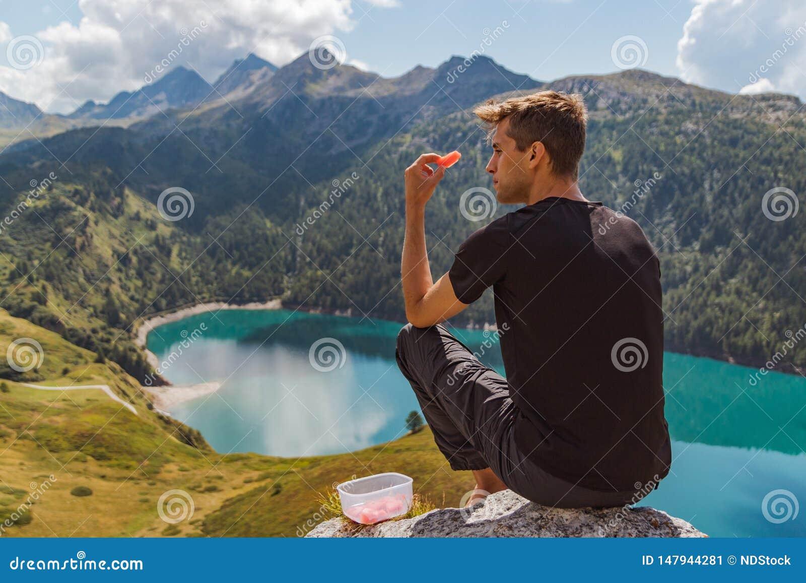 Le jeune homme assis sur une roche dans les montagnes mangent la pastèque et le regard au panorama
