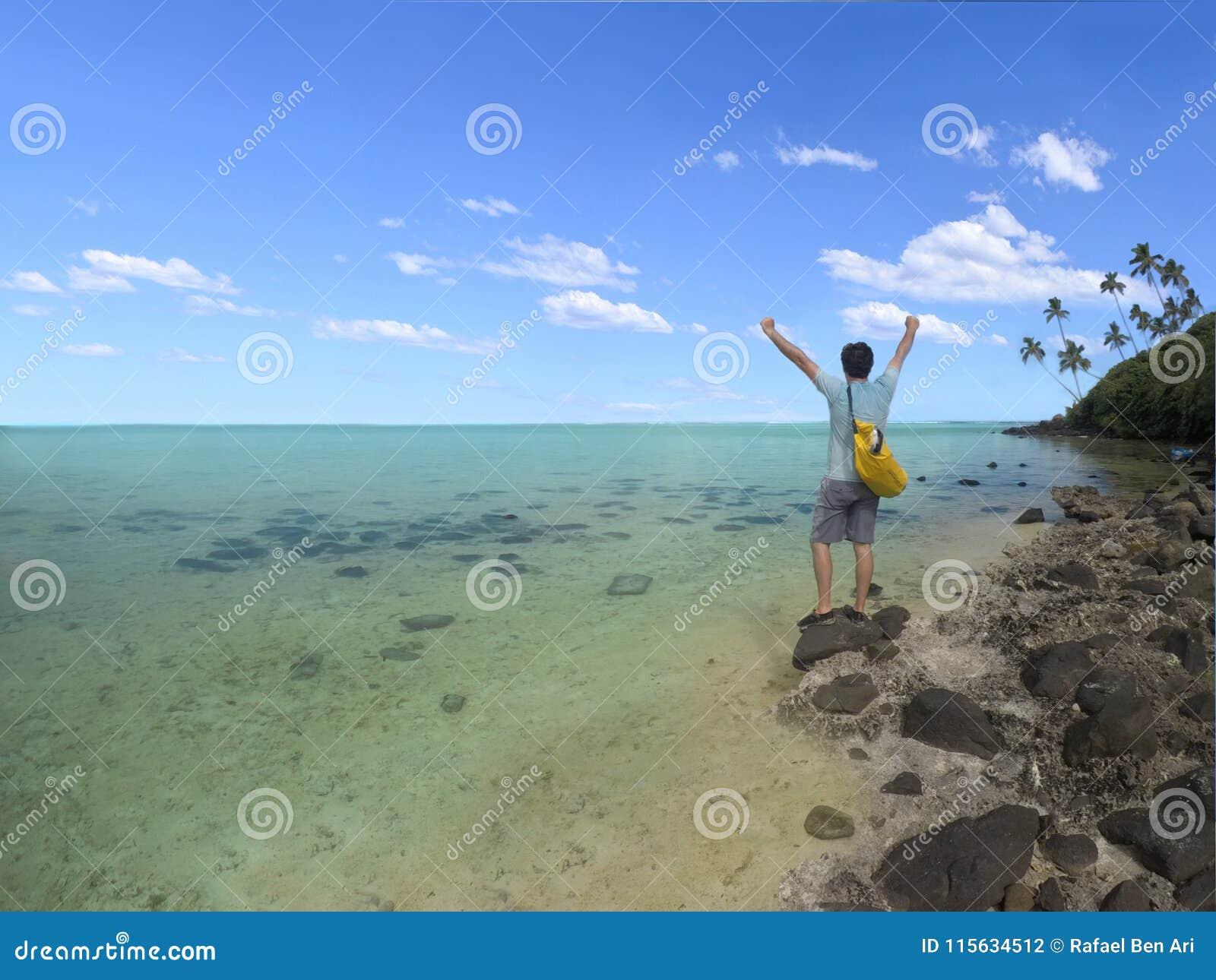 Le jeune homme avec le gagnant remet vers le haut des supports sur l îlot dans la lagune i de Muri